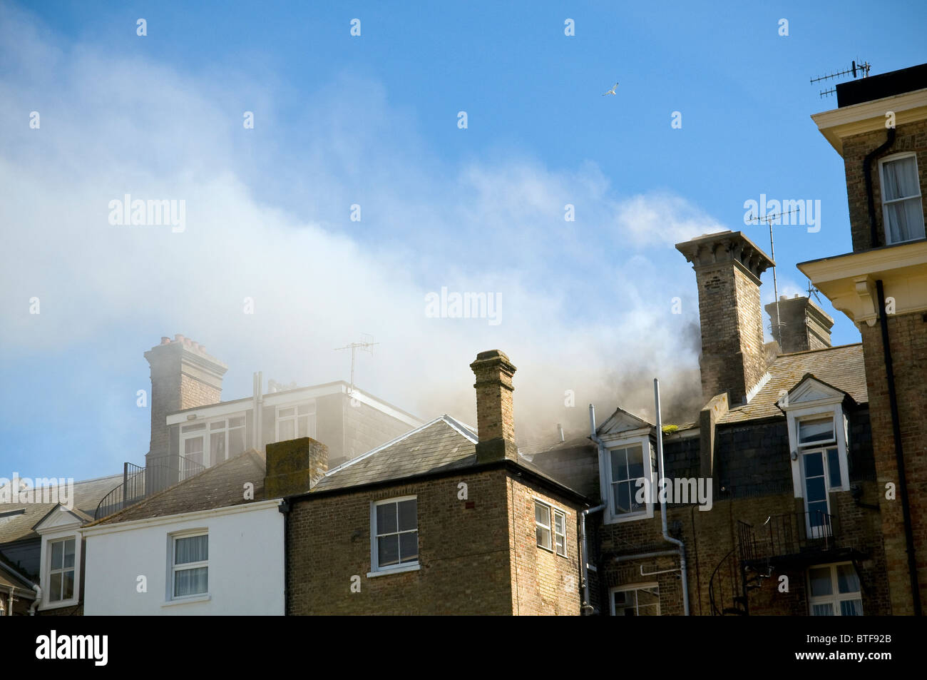 Smoke emerging from a fire in an upstairs flat in Worthing, West Sussex, UK - Stock Image