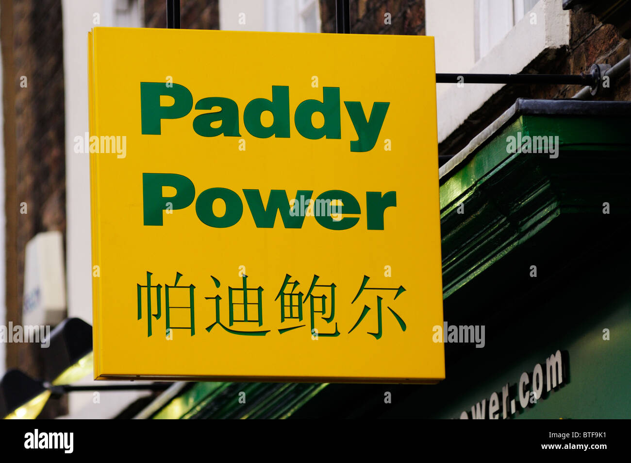 Bilingual Paddy Power Bookmaker sign, Gerrard Street, Chinatown, London, England, UK - Stock Image