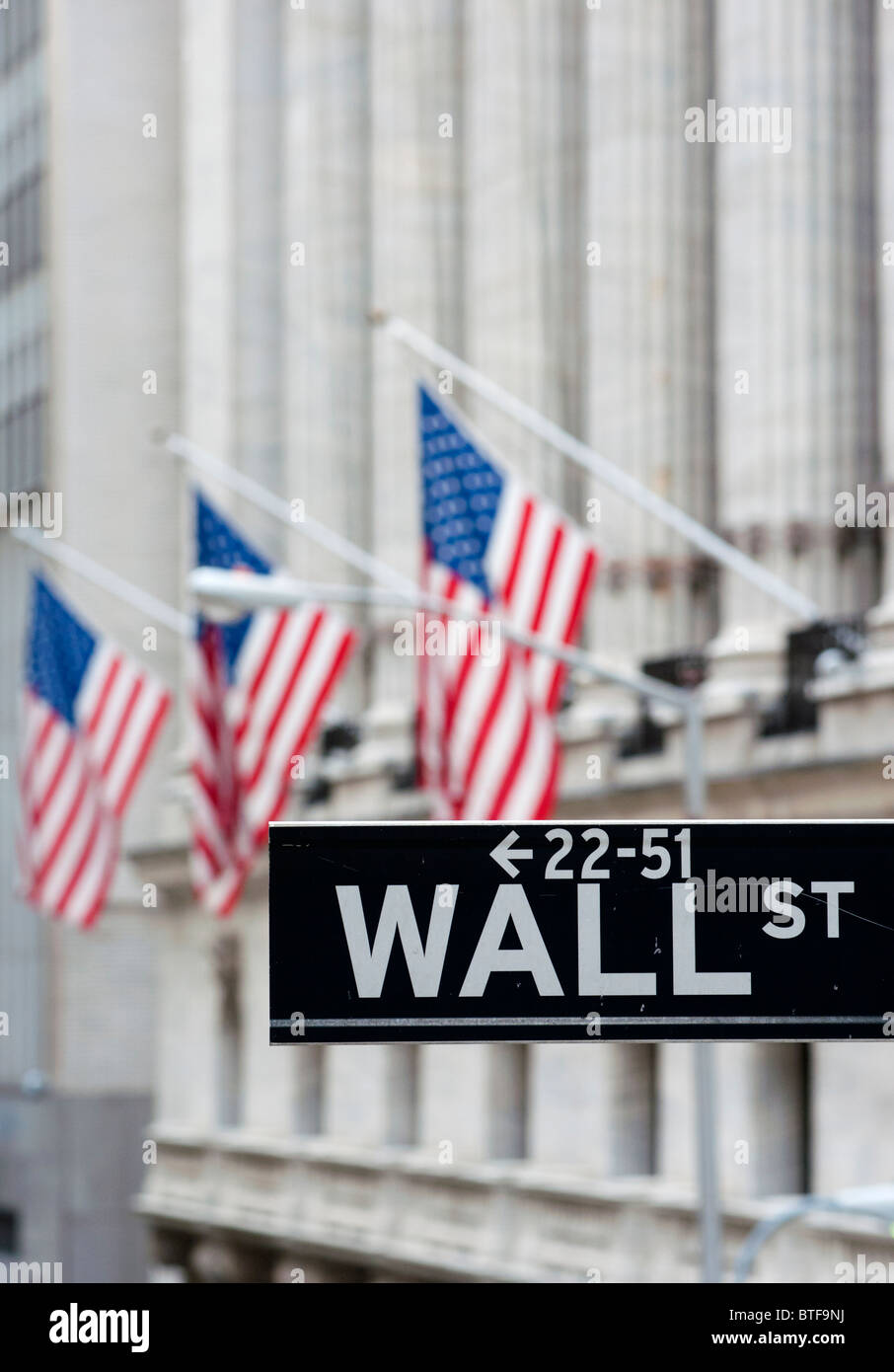 Detail of Wall Street sign with flags on Stock Exchange building to rear Manhattan New York City - Stock Image