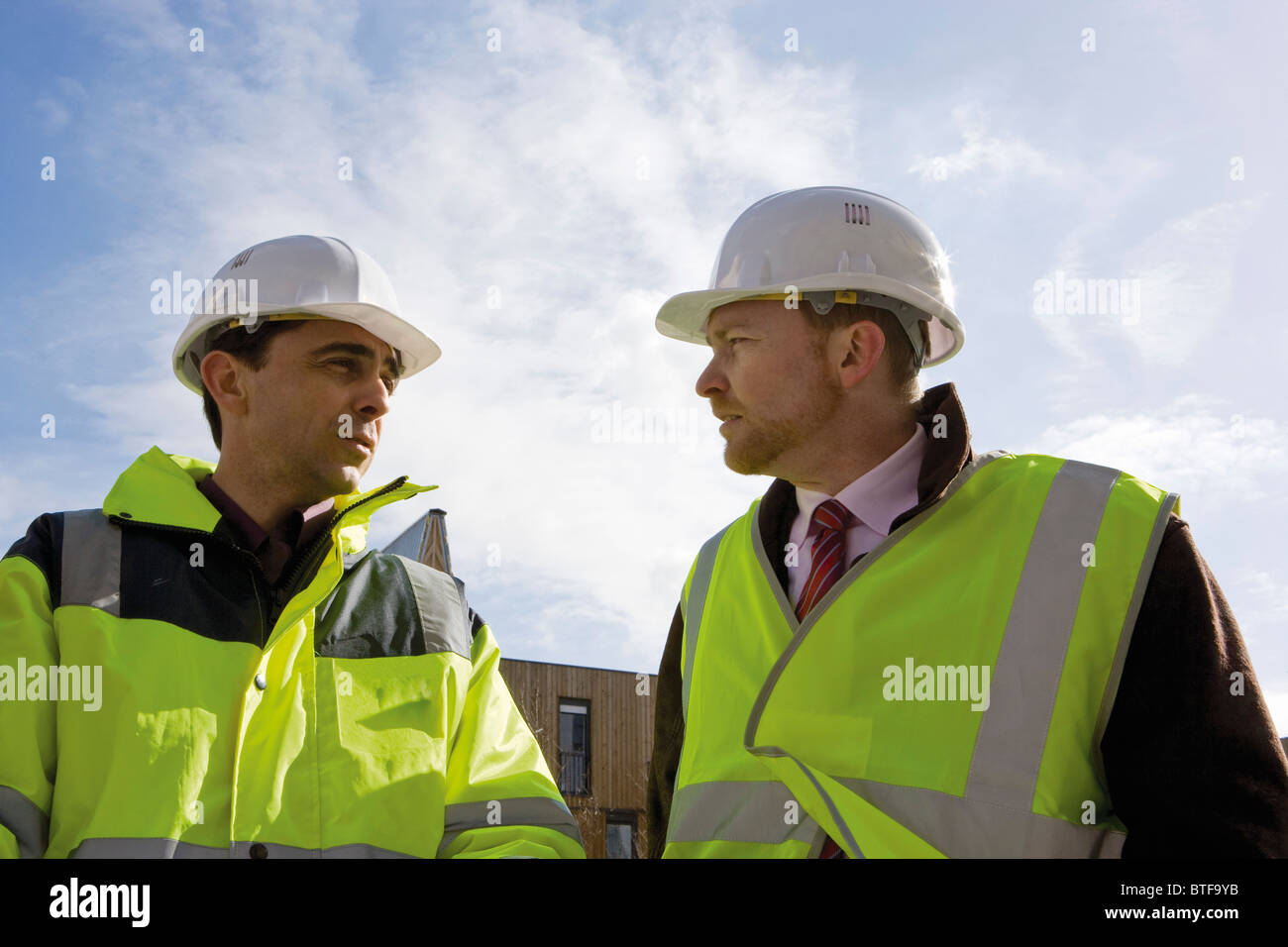 Building contractor and businessman in hard hat and reflective clothing - Stock Image