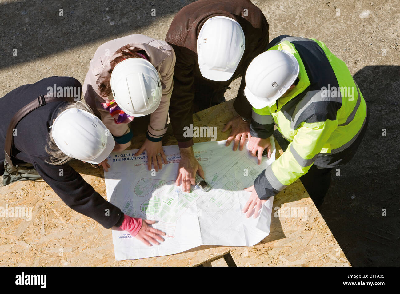 Architects meeting with building contractor at construction site to review blueprints - Stock Image
