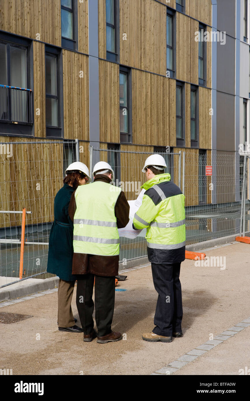 Building contractor and architects in discussion at construction site - Stock Image