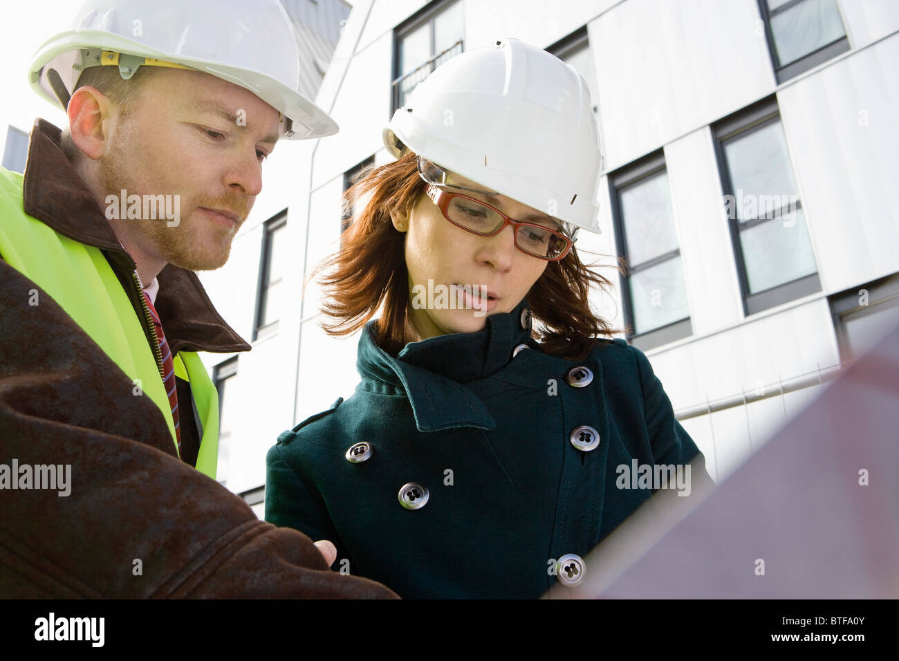 Architects looking at blueprint - Stock Image