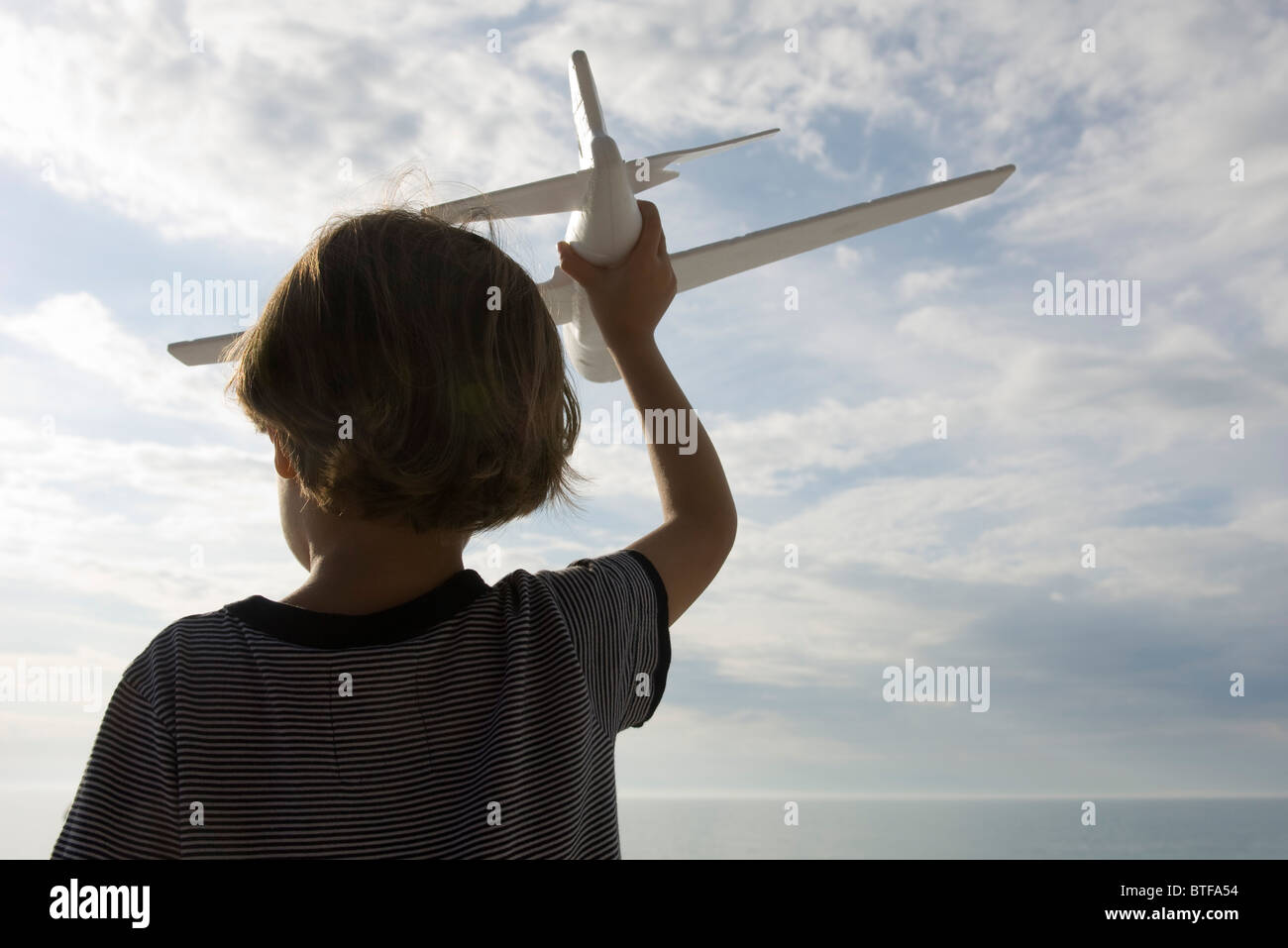 Boy playing with toy airplane, rear view - Stock Image