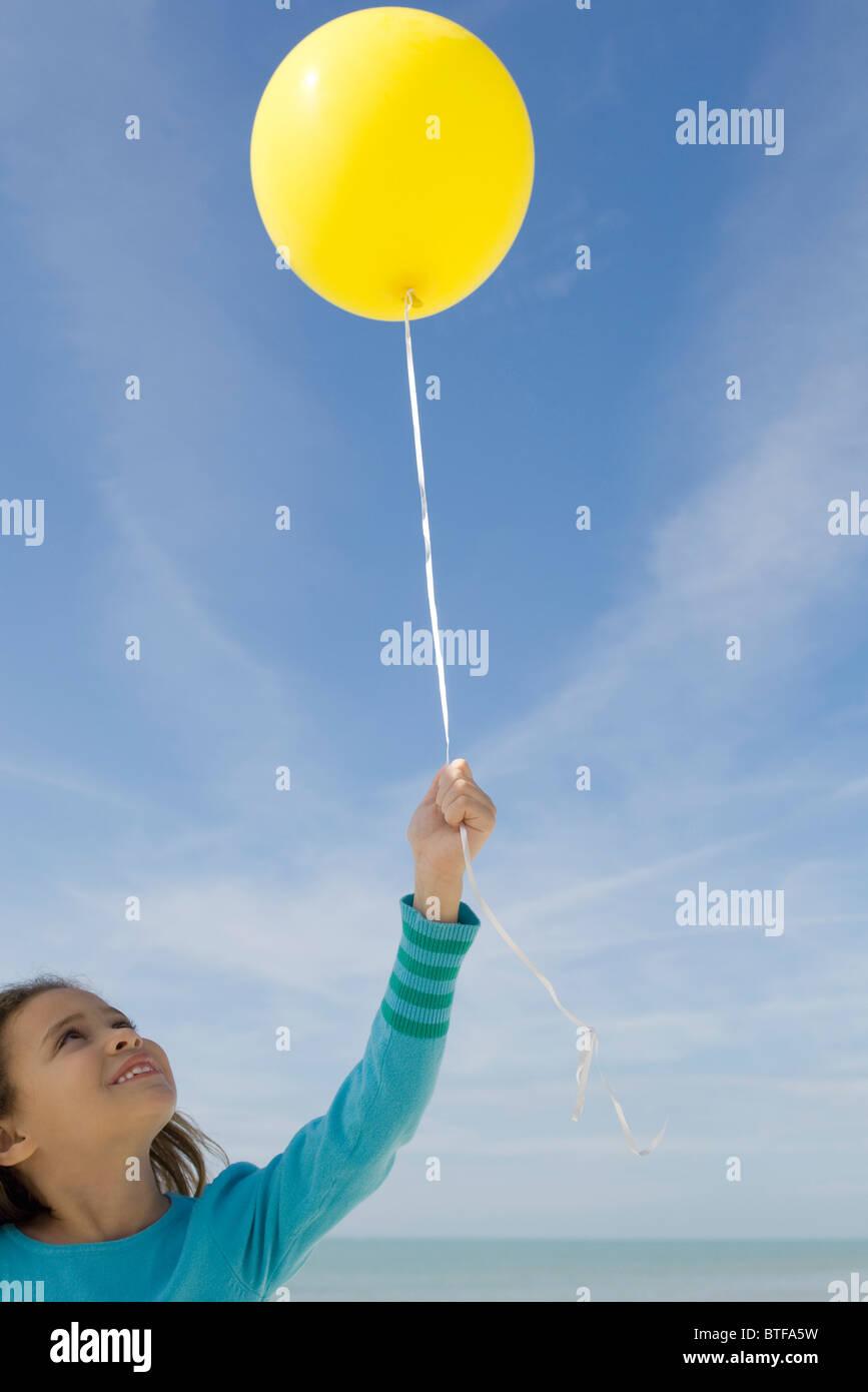 Girl holding balloon - Stock Image