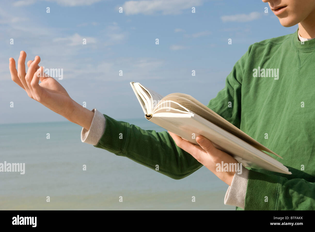 Young male reading aloud from book at the beach - Stock Image