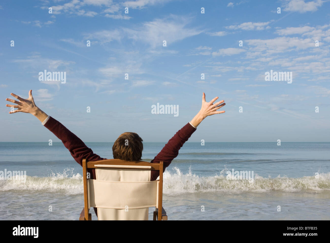 Young man sitting in chair on beach with arms raised, rear view - Stock Image