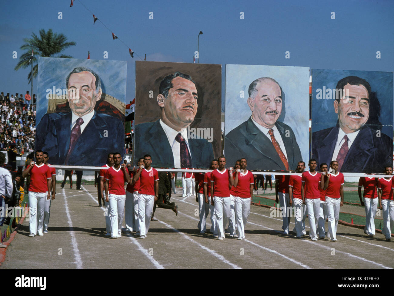 Giant portraits of Iraqi leaders,inc. Saddam Hussein are paraded around Baghdad stadium on Baath Party Day  rally - Stock Image