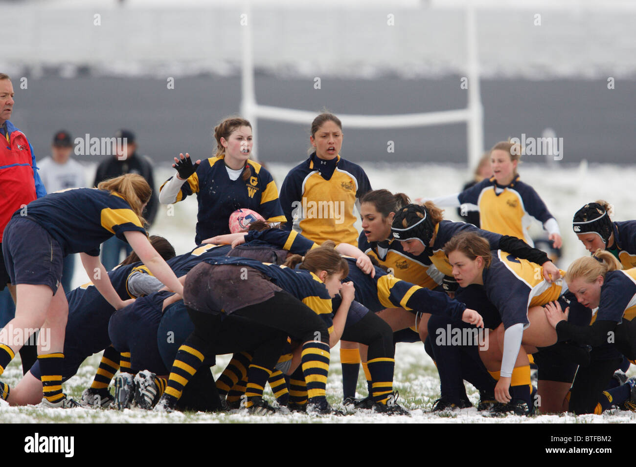 Naval Academy and George Washington University players set for a scrum during a women's rugby match. - Stock Image