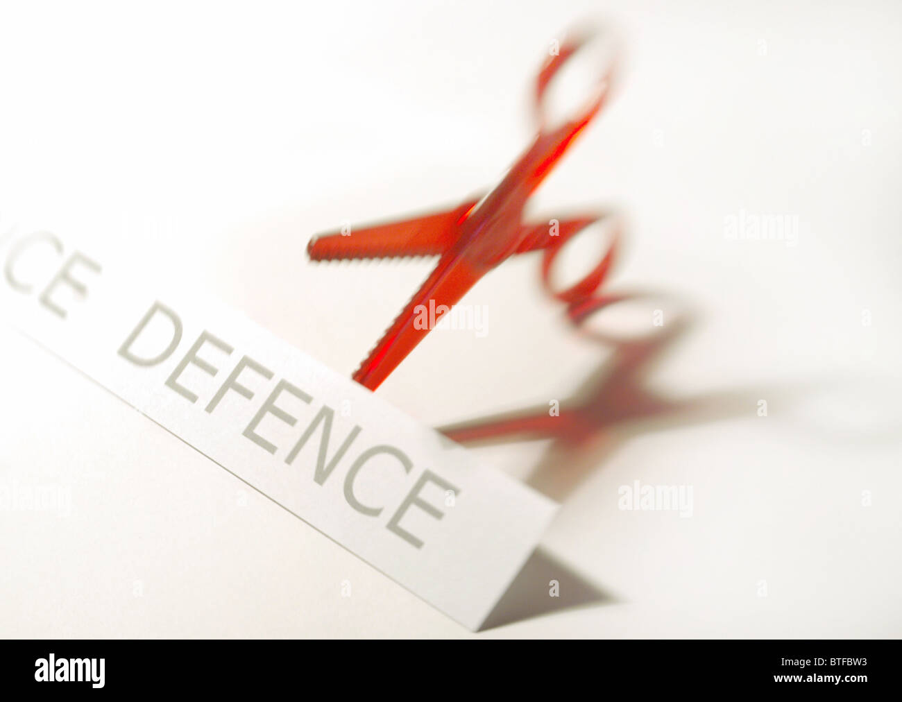 Defence cuts concept depicting red scissors and defence graphic. - Stock Image