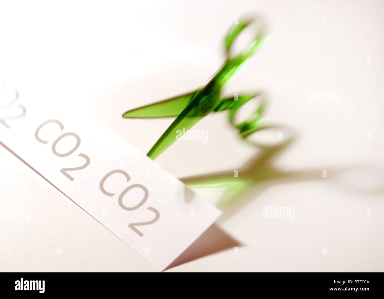 Carbon (CO2) reduction / cuts concept featuring green scissors cutting CO2 graphic. - Stock Image