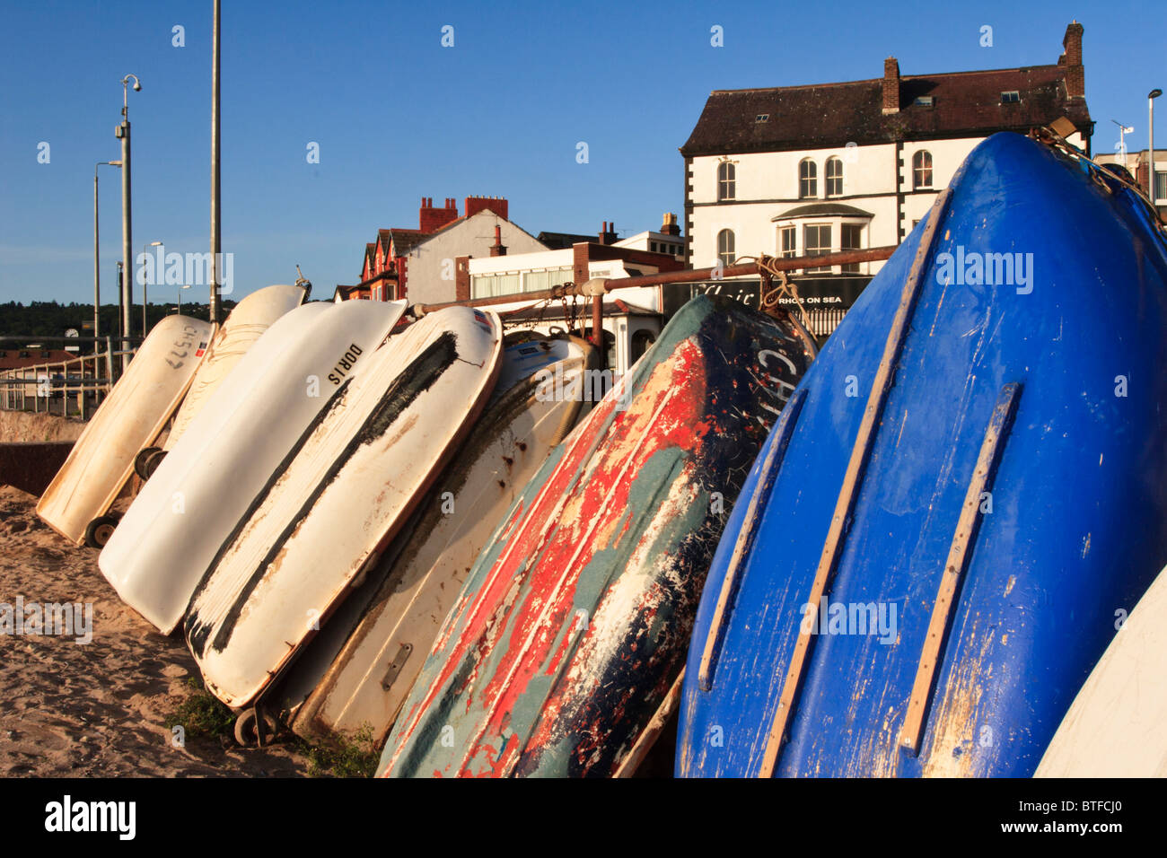 rowing boats tied up on beach at rhos on sea near colwyn bay in Conwy. - Stock Image