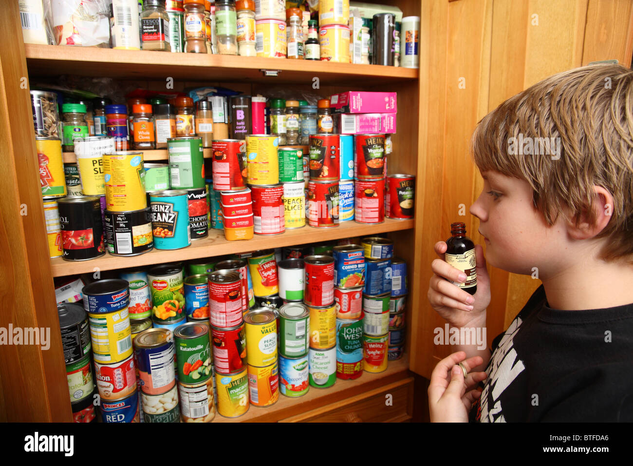 boy sniffing essence from food cupboard - Stock Image