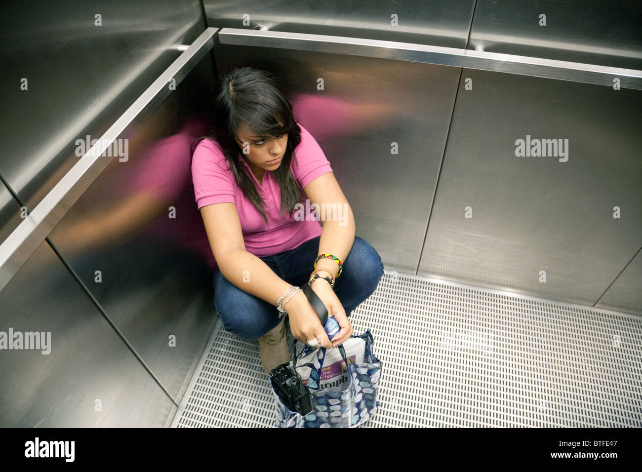 A teenage girl sitting in the corner of a lift - concept of Claustrophobia - Stock Image