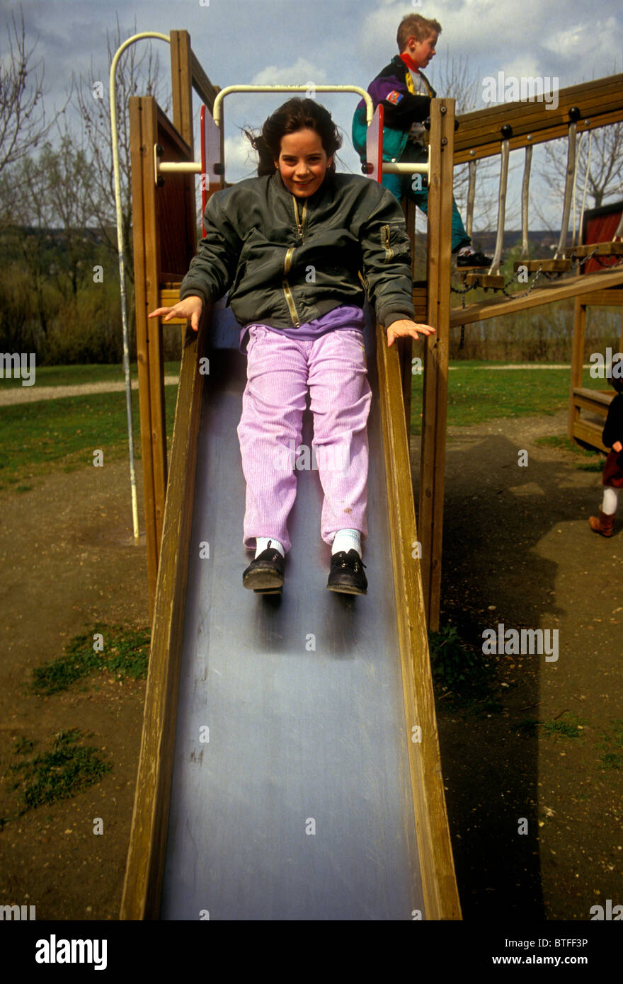 1, one, French girl, French, girl, young girl, female child, child, sliding down, sliding pond, playground, Verneuil - Stock Image