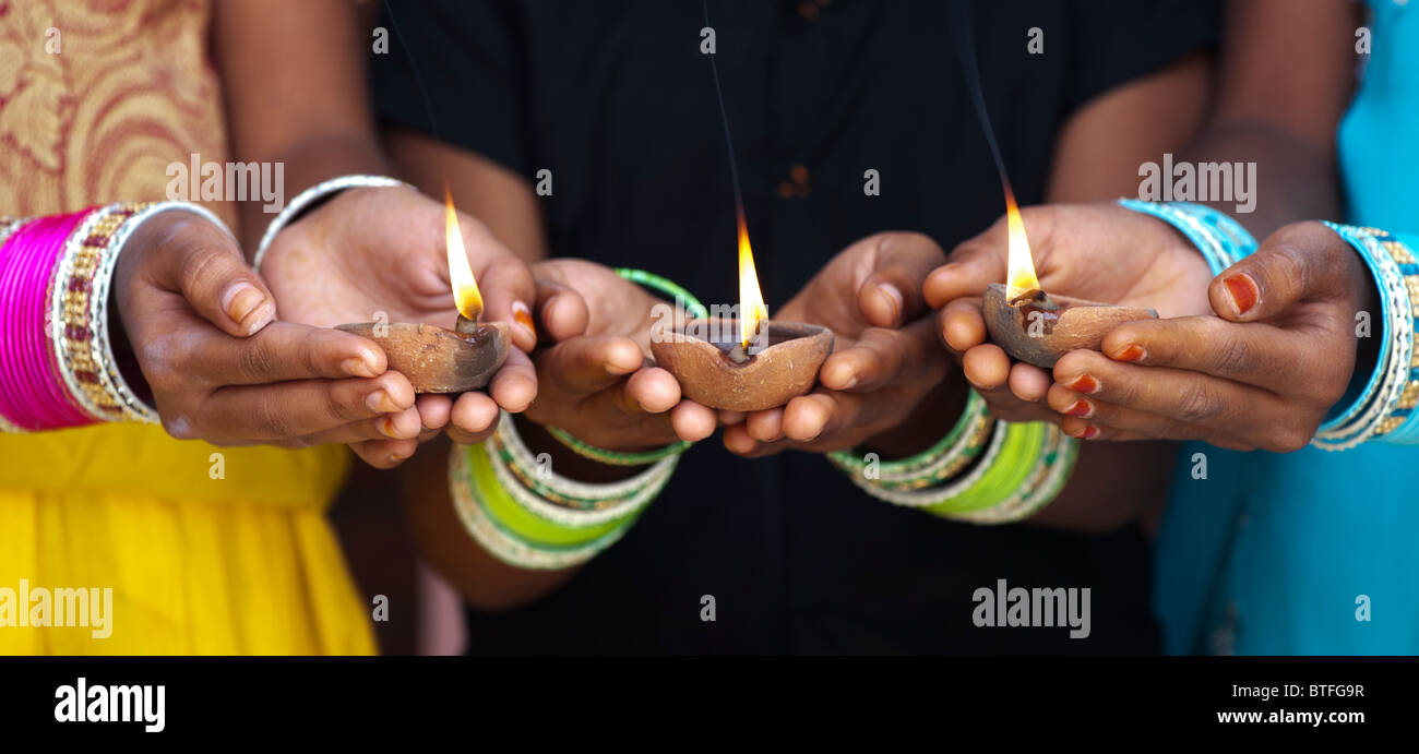 Young Indian girls holding lit oil lamps. India - Stock Image