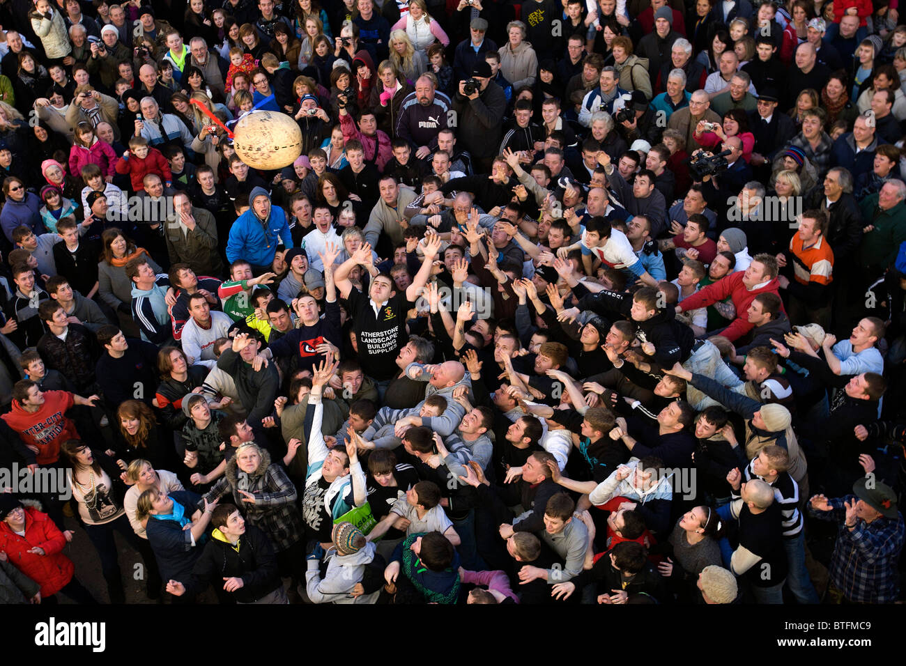 Atherstone Ball Game. Two teams attempt to kick and carry a leather ball to either end of Long Street on Shrove - Stock Image