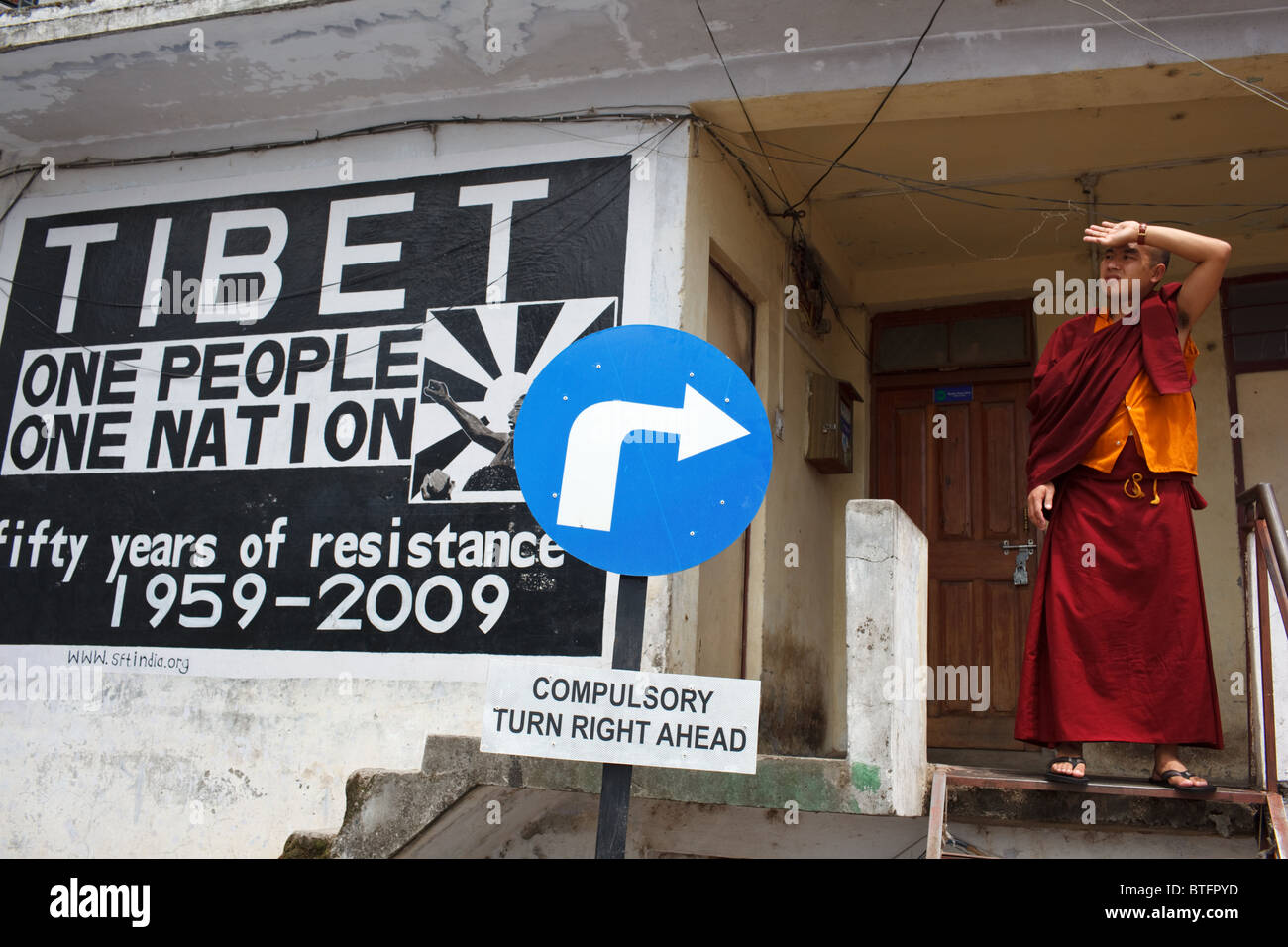 A Buddhist Tibetan monk standing by a 'Free Tibet' style mural McLeod Ganj, India - Stock Image