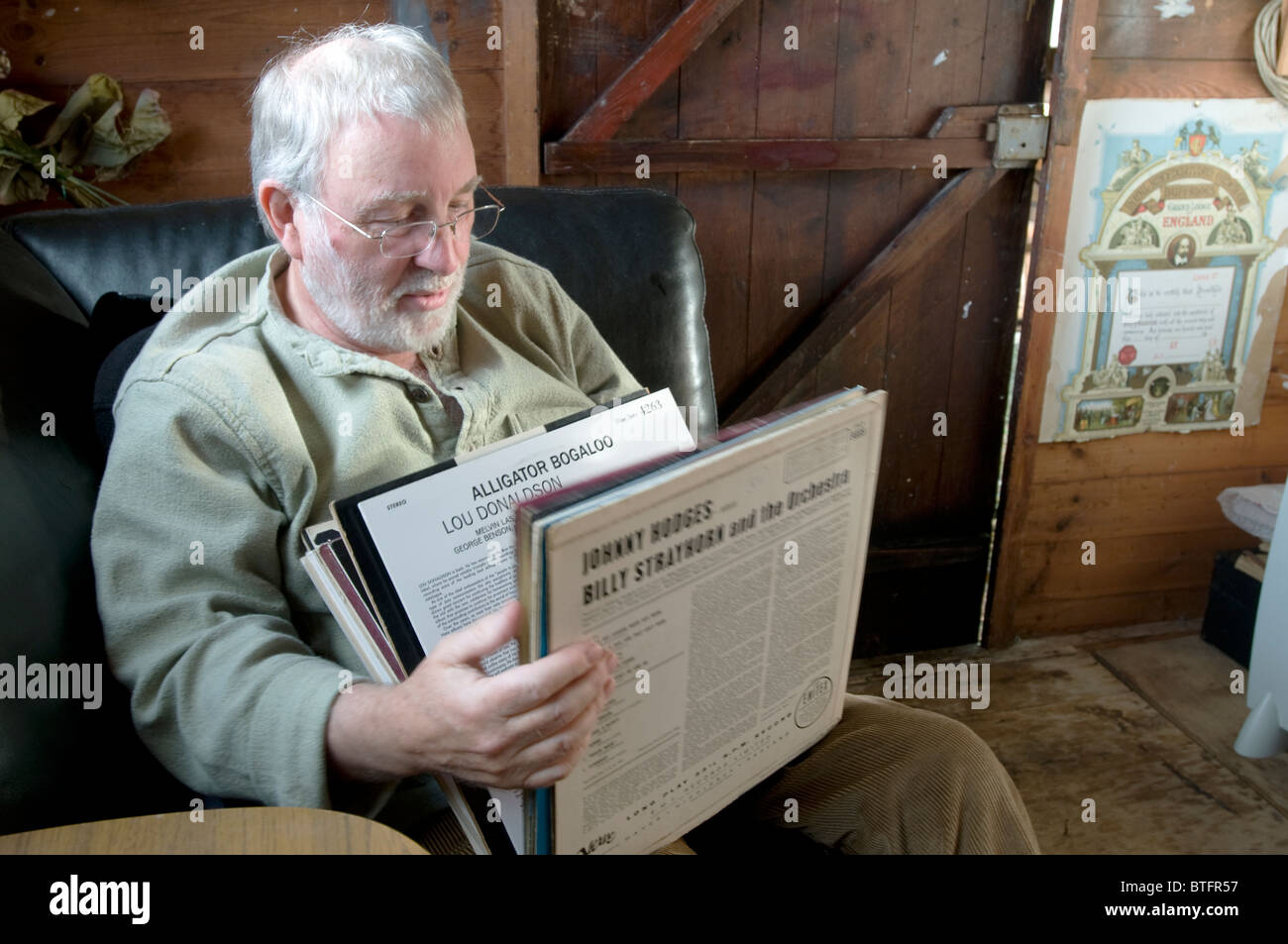 A 65 year old jazz enthusiast looks through records in his shed - Stock Image