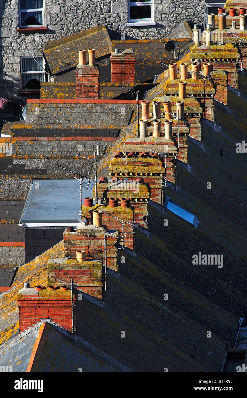 A row of chimneys and rooftops in a long terrace of houses. Dorset, UK October 2010 - Stock Image