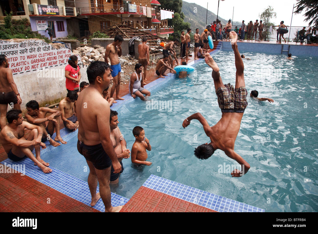 37d4ff2b2a A group of young men jumping into the public swimming pool in Bhagsu,  Mcleod Ganj