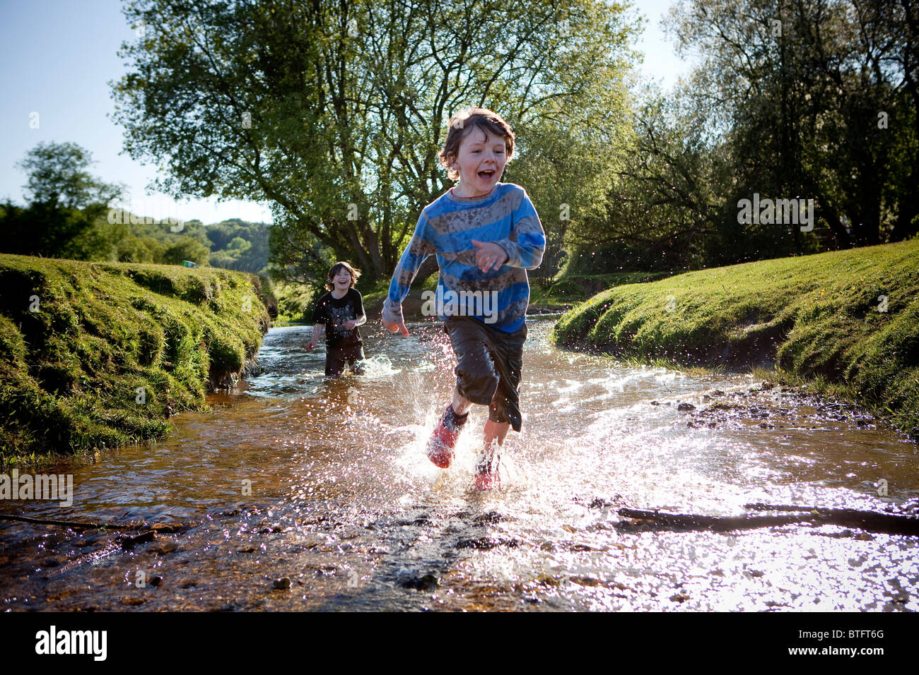 Two boys running in stream - Stock Image