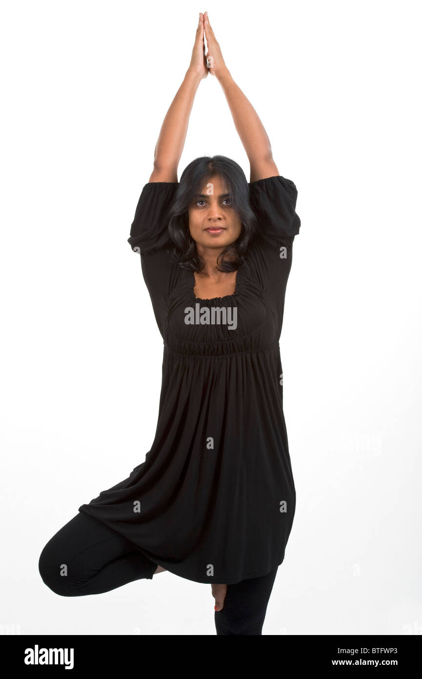 Woman Of Indian Descent Holding A Yoga Pose On White Background Stock Photo Alamy