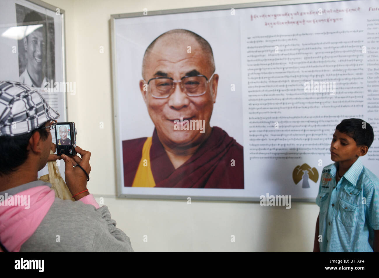 A person takes a photo of a portrait of Dalai Lama in a museum in McLeod Ganj, Dharamshala, India - Stock Image