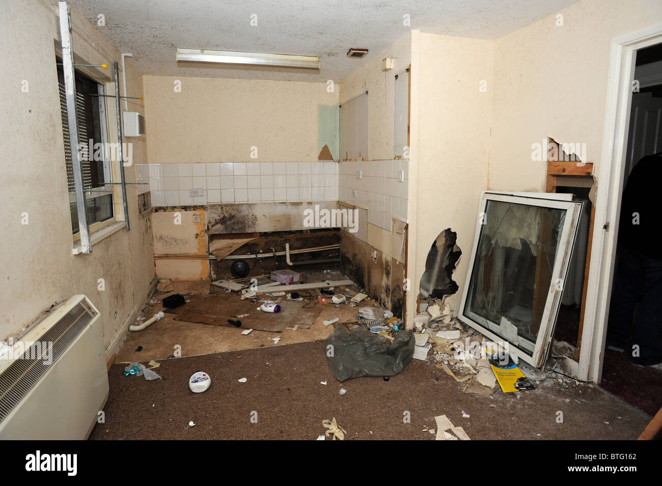Damage left to a large council owned house after illegal squatters wrecked it - Stock Image