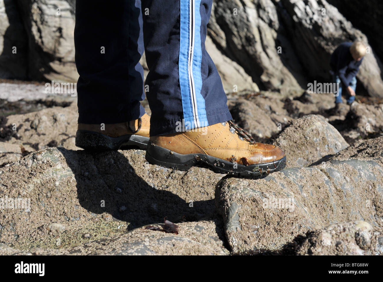 Two children in walking boots scrambling about on rocks and in rock pools at a seaside cove in autumn sunshine - Stock Image