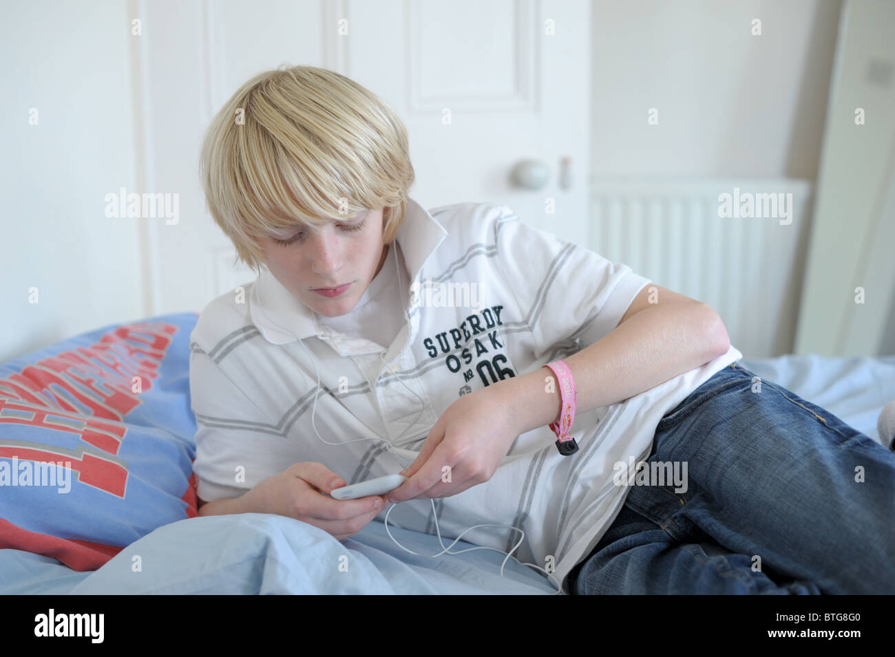 Teenage Boy Alone In His Bedroom Lying On The Bed Concentrating On