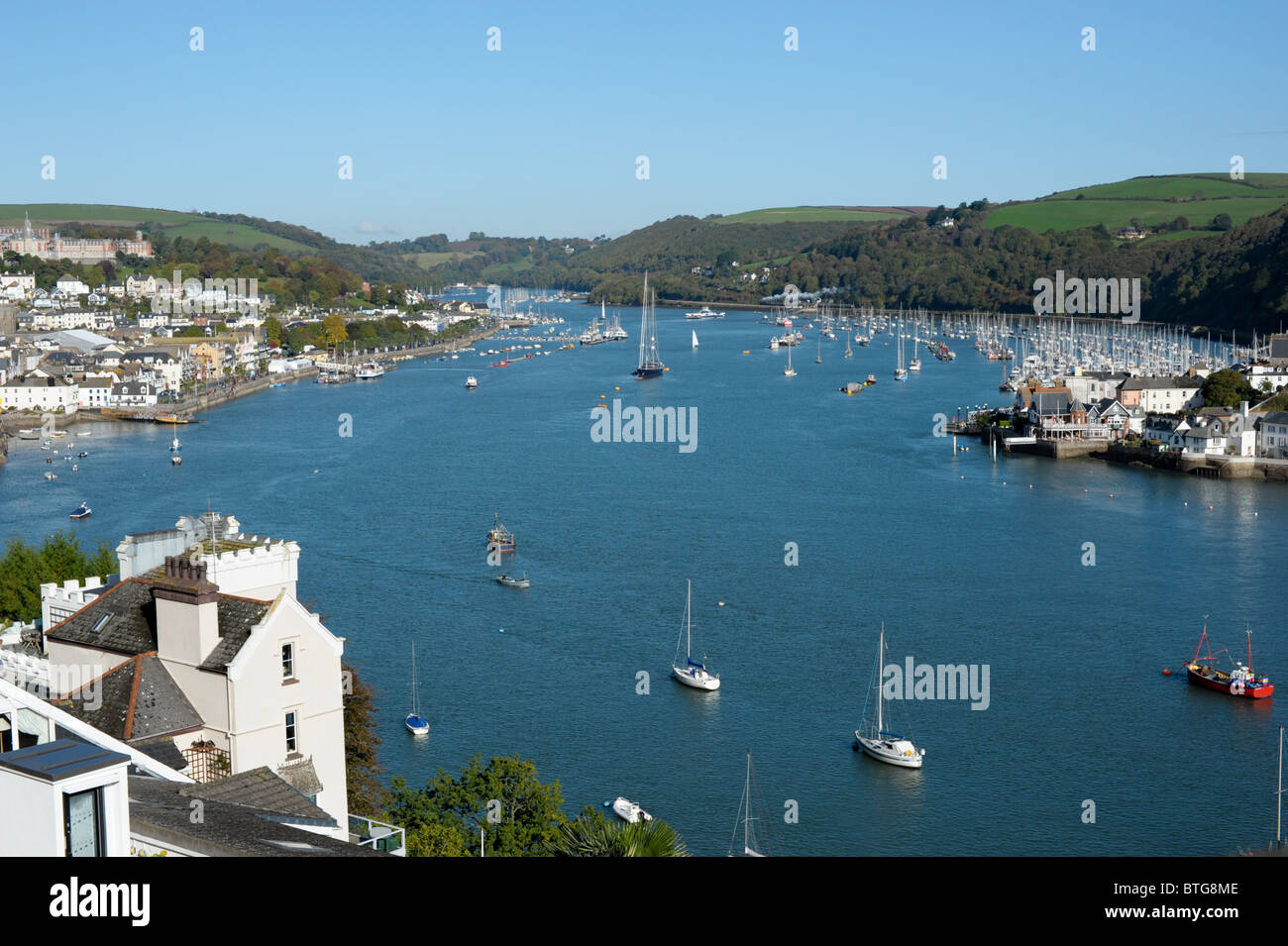 View from above looking up the River Dart dotted with sailing boats with clear blue skies and the Royal Naval College - Stock Image