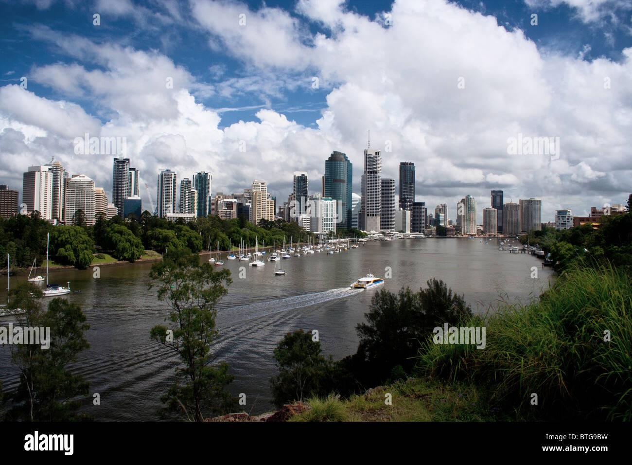 A CityCat plies the Brisbane River heading towards the subtropical capital of Queensland - Stock Image