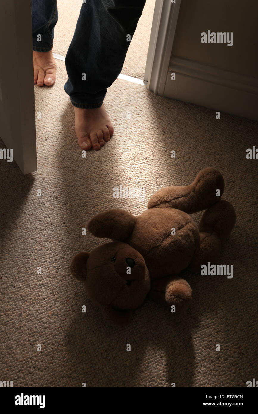 Bare footed man, face not shown walks, into a child's bedroom with a teddy bear on the floor (no child). - Stock Image