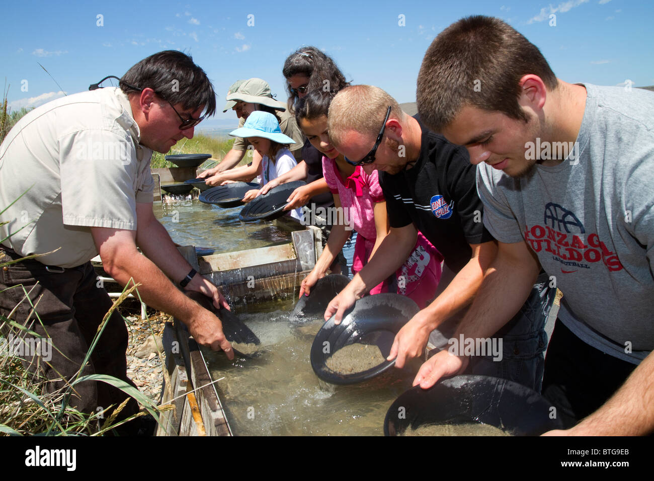 Visitors pan for gold in a demonstration sluice at the National Historic Oregon Trail Interpretive Center at Baker - Stock Image