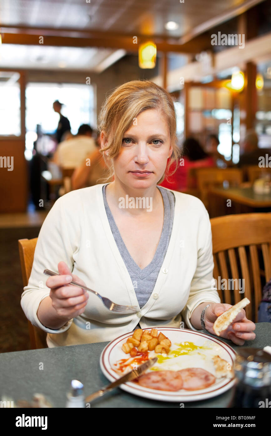 Woman eating breakfast at a diner.  Winnipeg, Manitoba, Canada. - Stock Image