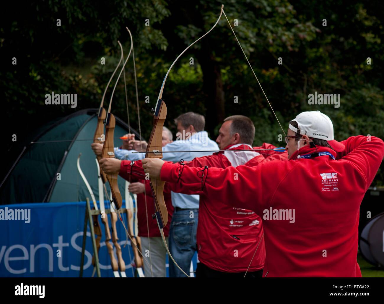 Males using bows and arrows firing at target, Edinburgh, Scotland UK, Europe - Stock Image