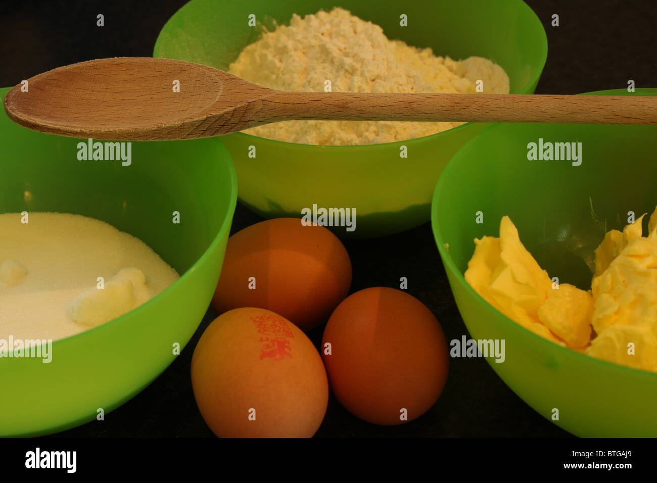 Cake ingredients; flour, sugar, butter and eggs with wooden spoon Stock Photo