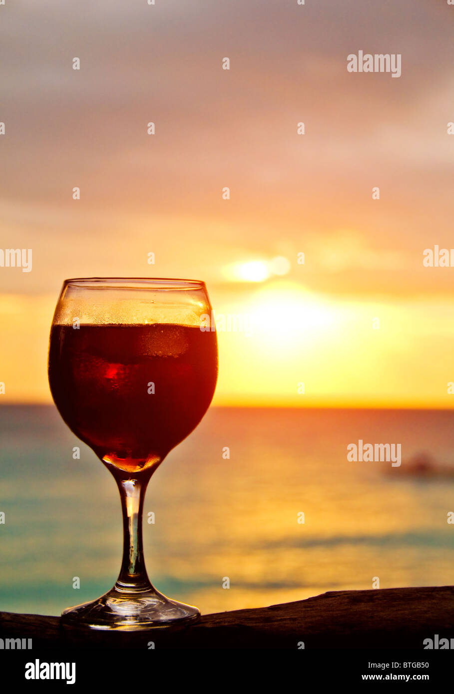 A glass of vine at the rock on romantic beach Stock Photo