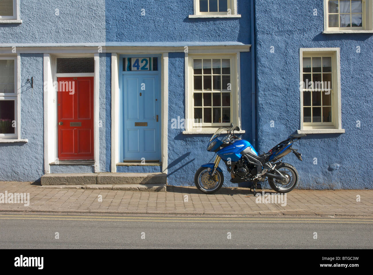 Motorbike and terraced houses, Soutergate, Ulverston, Cumbria, England UK - Stock Image
