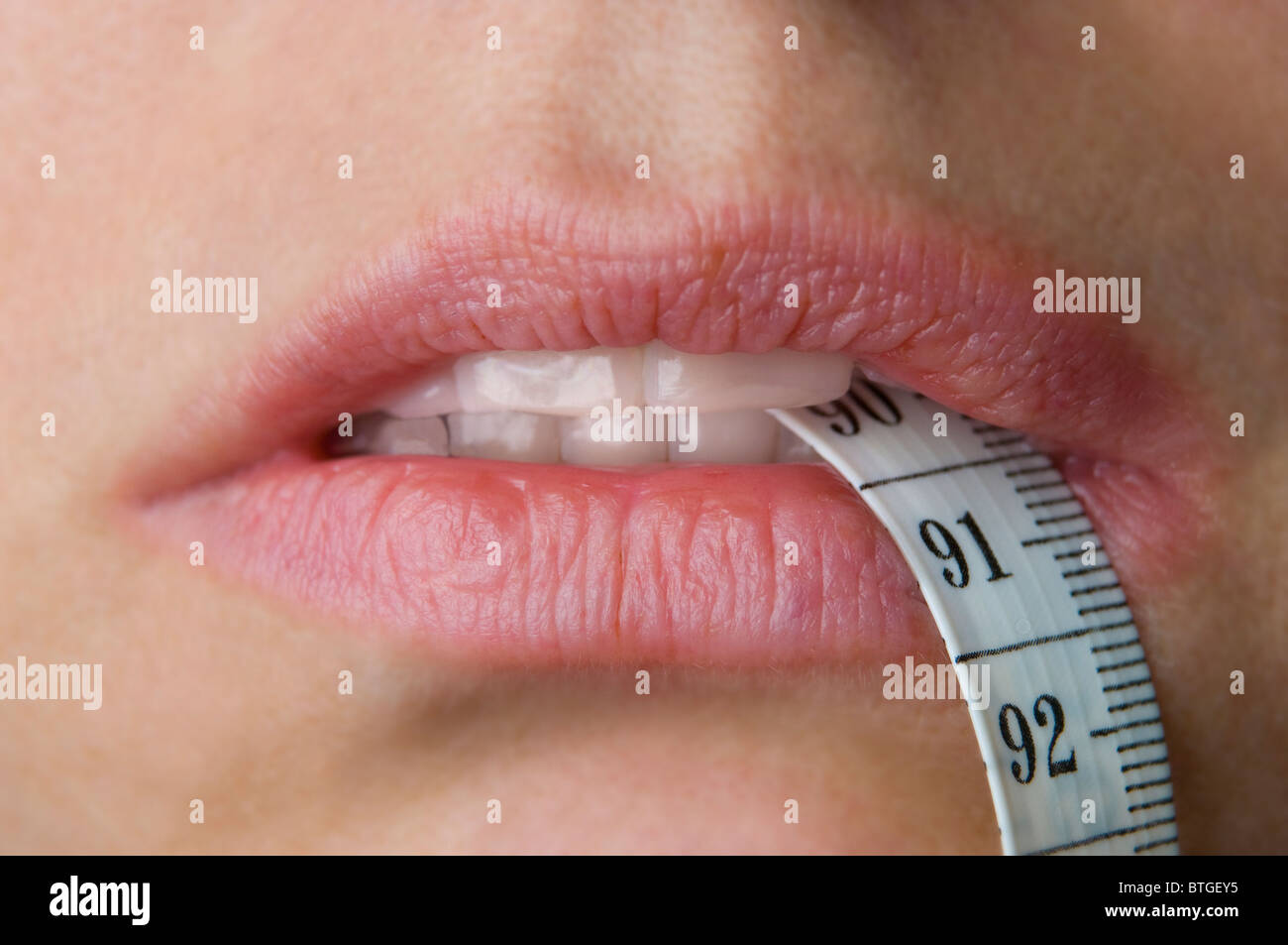 womans mouth with tape measure indicating weight loss or gain - Stock Image