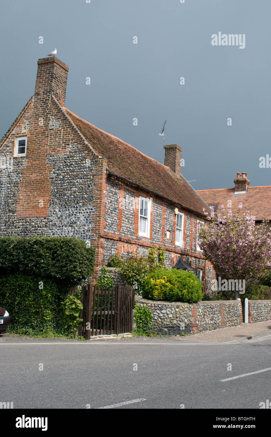 The sun shines on a flint and brick house, in the original part of Rustington village in West Sussex. - Stock Image