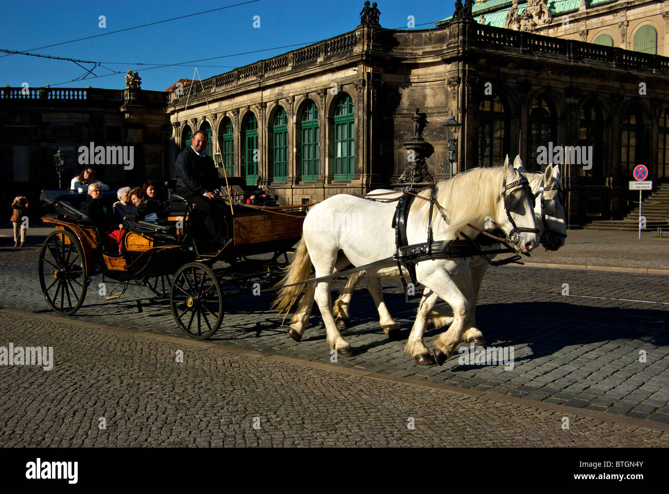 Tourists taking tour of old historic Dresden Altstadt aboard gleaming wooden horse drawn carriage - Stock Image