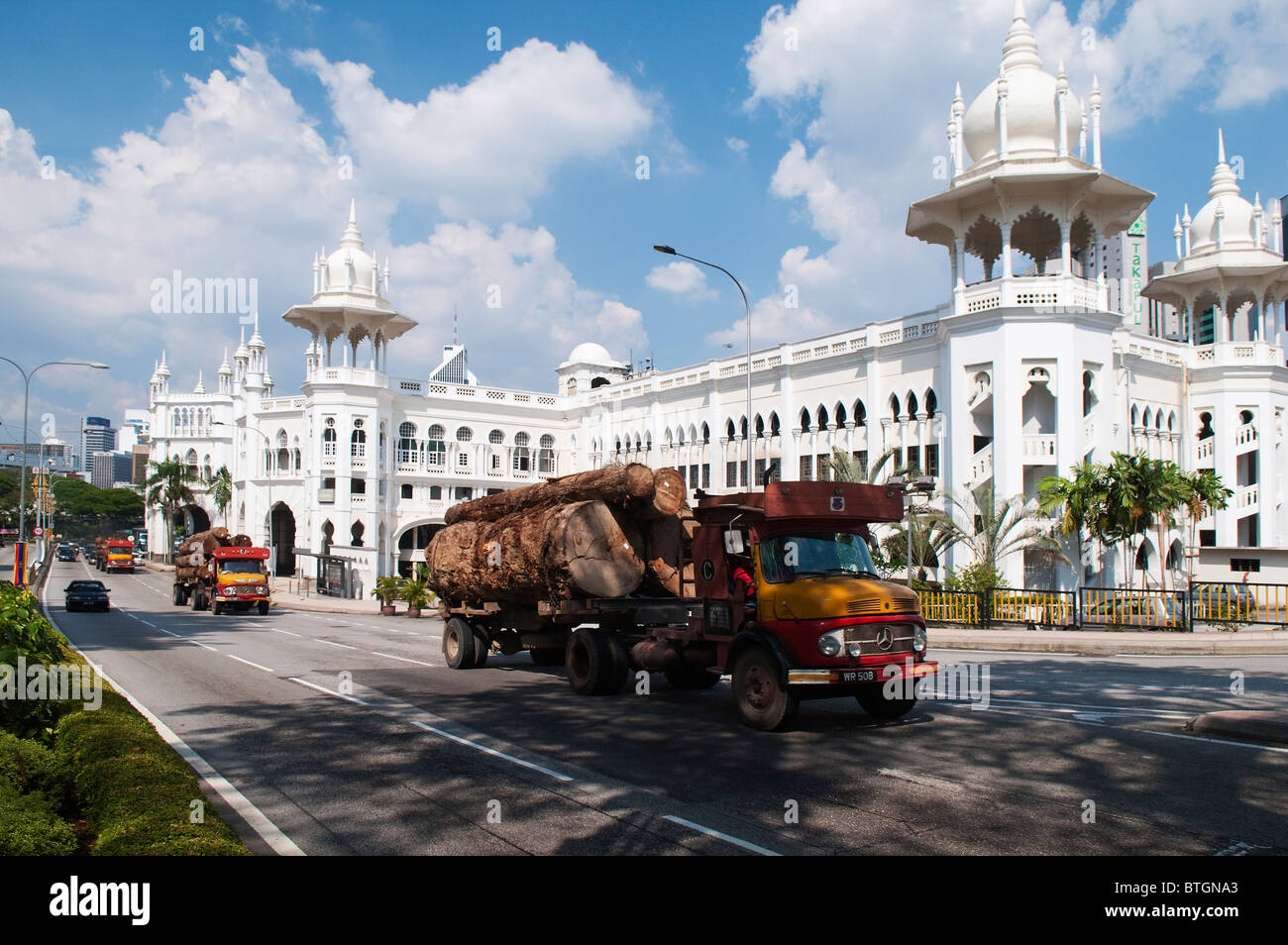 Logging trucks driving in front of the Moorish and Mogul inspired Old KL Train Station from 1911 in Kuala Lumpur, - Stock Image