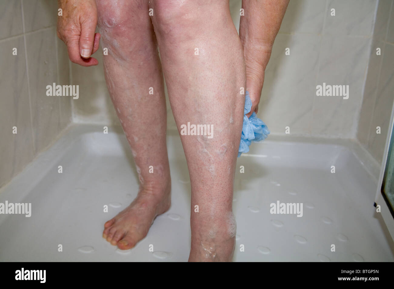 Close up elderly woman washing leg in a shower cubicle using blue body puff - Stock Image