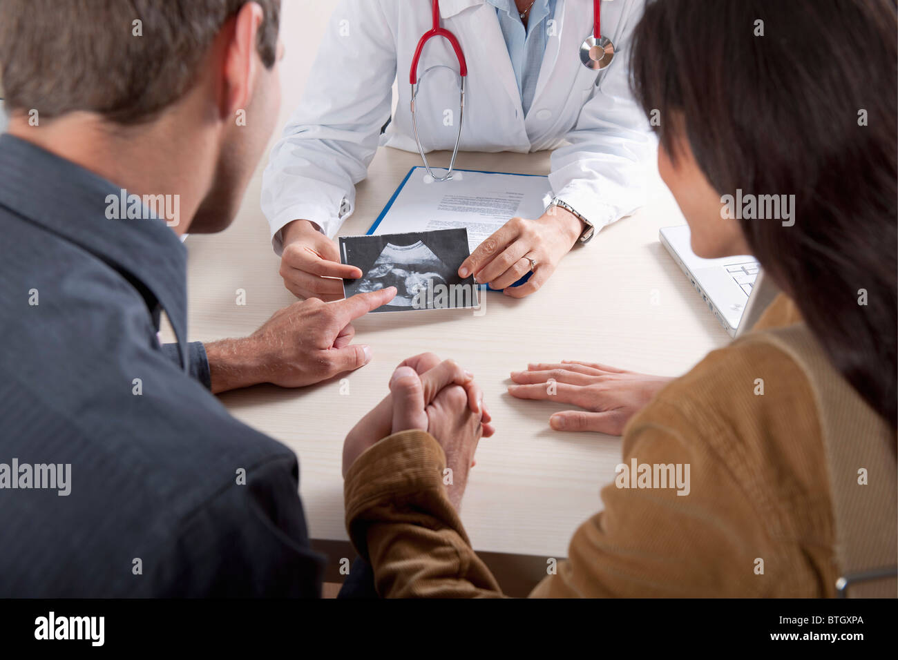 Doctor with ultrasound and couple - Stock Image