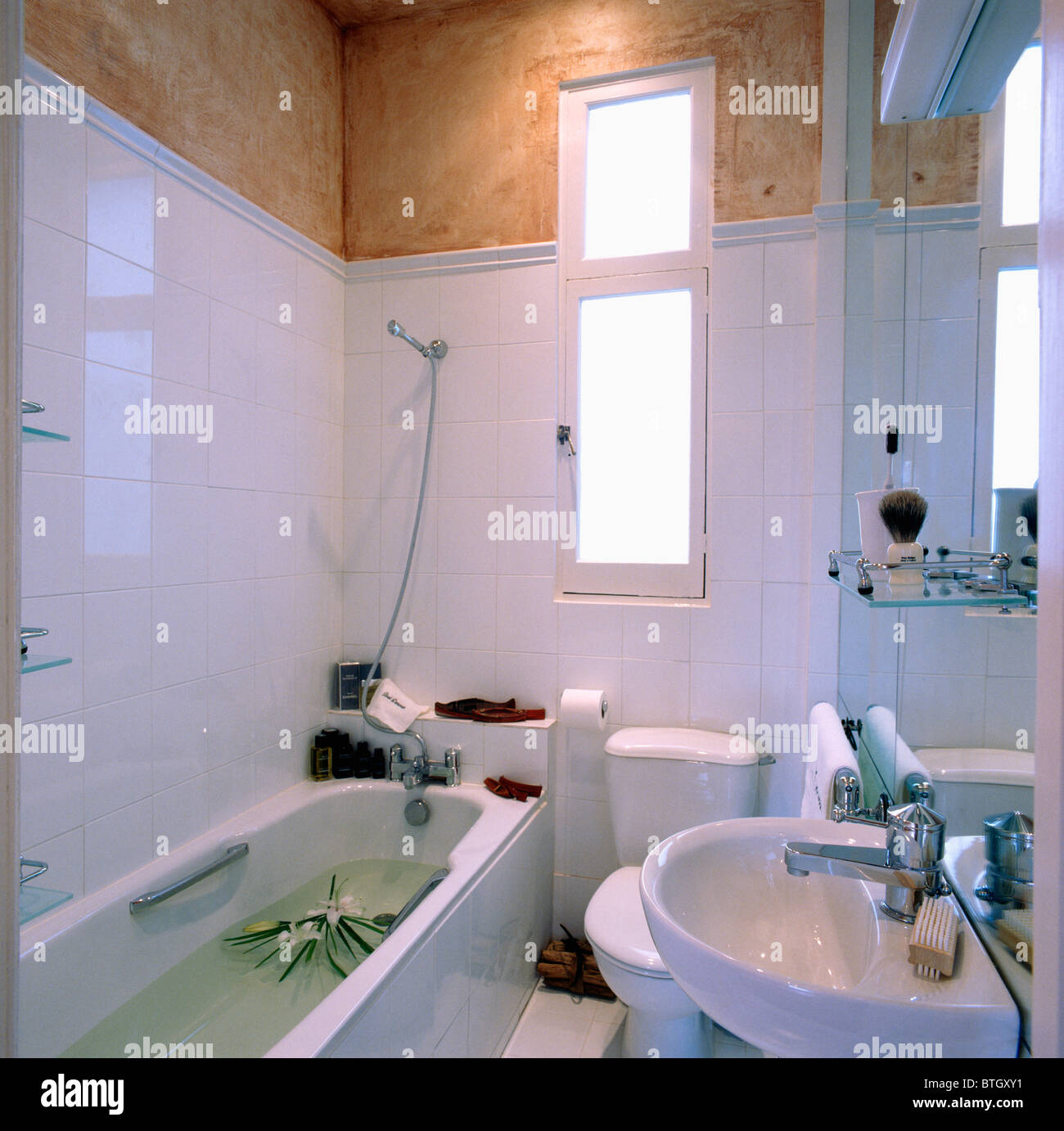 White tiled walls in modern economy-style bathroom with water in ...