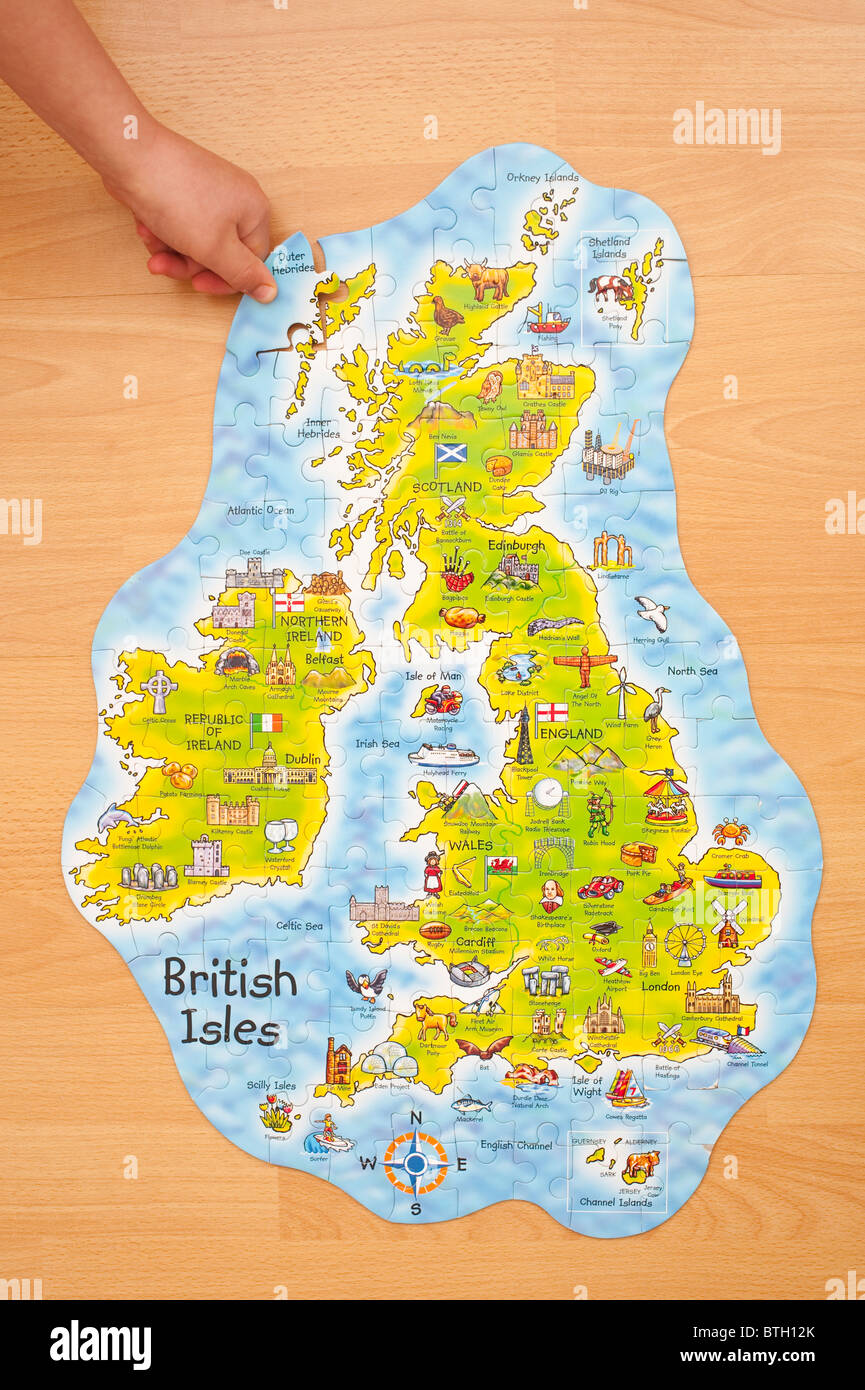 A MODEL RELEASED child puts in the last piece of a jigsaw of the British Isles - Stock Image
