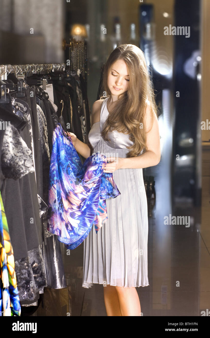 beautiful rich woman chooses a dress in a boutique - Stock Image