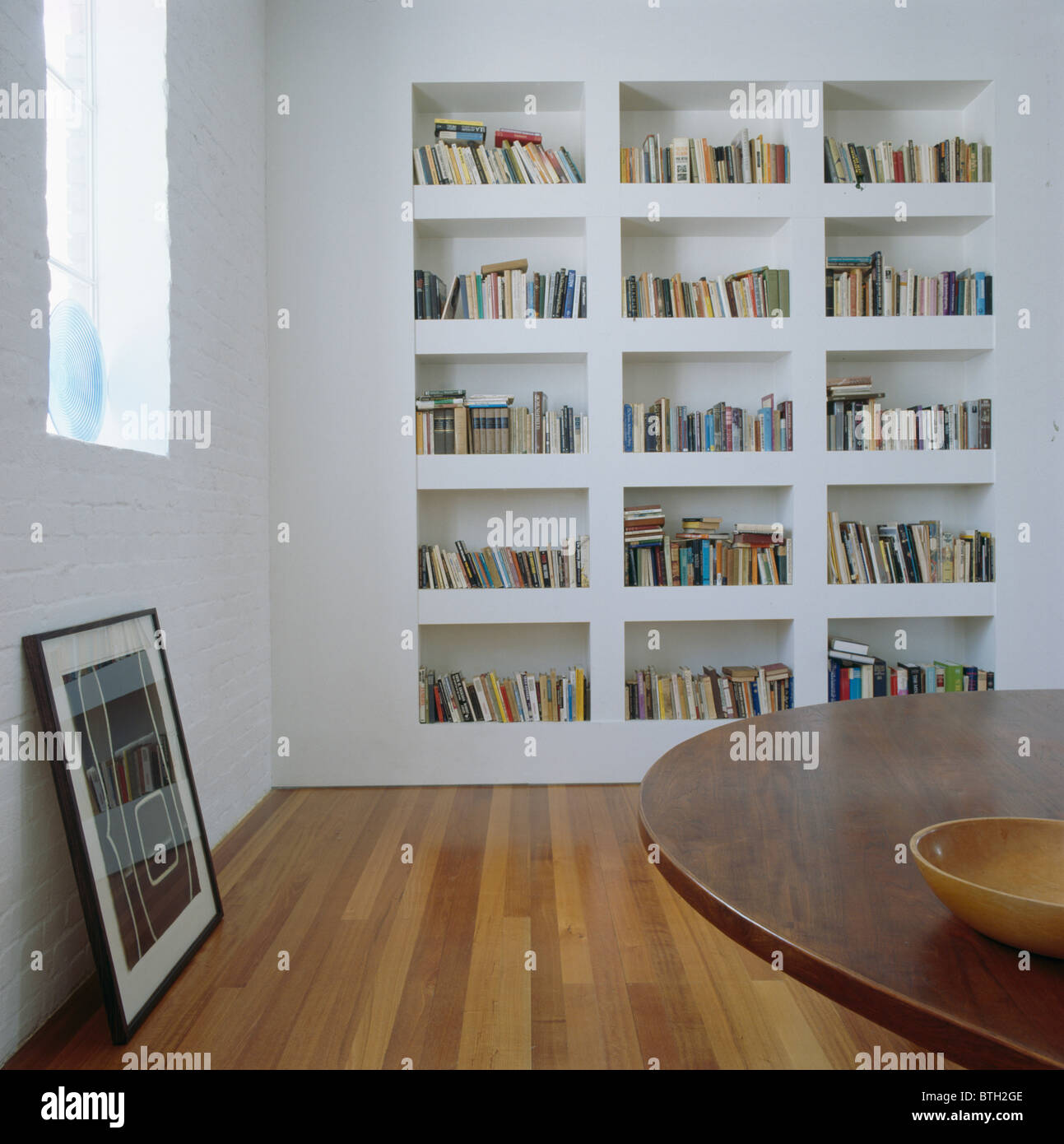 White recessed bookshelves in modern white dining room with picture propped up on wooden floor - Stock Image